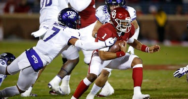 Oklahoma quarterback Jalen Hurts (1) carries past TCU safety Trevon Moehrig (7) and linebacker Garret Wallow (30) in the first quarter of an NCAA college football game in Norman, Okla., Saturday, Nov. 23, 2019.
