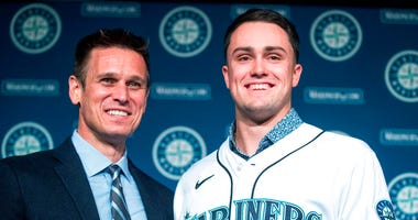Seattle Mariners general manager Jerry Dipoto, left, and new first baseman Evan White pose for photographs with White's new jersey after a news conference at T-Mobile Park Monday, Nov. 25, 2019 in Seattle.