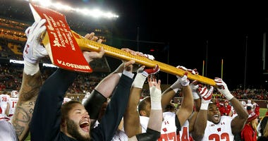 Wisconsin players hold up Paul Bunyan's Axe up after winning 31-0 against Minnesota