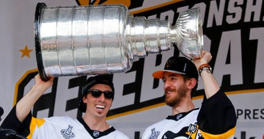 Pittsburgh Penguins goalies Marc-Andre Fleury, left, and Matt Murray hold the Stanley Cup on stage after riding in the Stanley Cup victory parade in Pittsburgh.