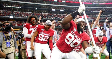Oklahoma defensive lineman Neville Gallimore (90) plants a University of Oklahoma flag after the Sooners 30-23 overtime win over Baylor in an NCAA college football game for the Big 12 Conference championship, Saturday, Dec. 7, 2019, in Arlington, Texas.