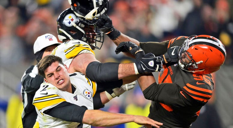 Cleveland Browns defensive end Myles Garrett hits Pittsburgh Steelers quarterback Mason Rudolph (2) with a helmet during the second half of an NFL football game, Nov. 14, 2019, in Cleveland.