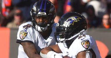 Baltimore Raven quarterback Lamar Jackson hands off to running back Mark Ingram during an NFL football game against the Cleveland Brown at FirstEnergy Stadium in Cleveland on Sunday, Dec. 22, 2019.