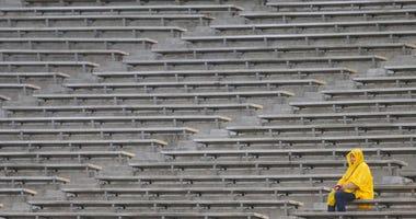 A fan watches Boston College play Cincinnati in the rain during the first half of the Birmingham Bowl NCAA college football game Thursday, Jan. 2, 2020, in Birmingham, Ala.