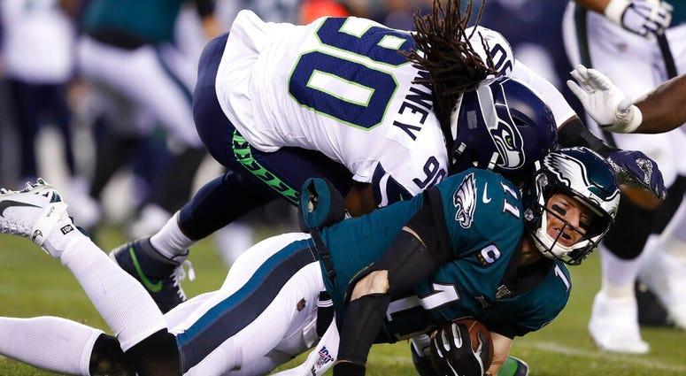 Seattle Seahawks' Jadeveon Clowney (90) hits Philadelphia Eagles' Carson Wentz (11) during the first half of an NFL wild-card playoff football game, Sunday, Jan. 5, 2020, in Philadelphia.