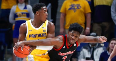 Louisville's Darius Perry (2) reaches for the ball held by Pittsburgh's Xavier Johnson during the first half of an NCAA college basketball game Tuesday, Jan. 14, 2020, in Pittsburgh.