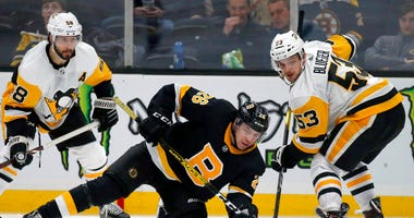 Boston Bruins center Par Lindholm (26) and Pittsburgh Penguins center Teddy Blueger (53) look to make a play for the puck during the third period of an NHL hockey game, Thursday, Jan. 16, 2020, in Boston.