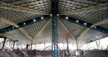 the interior of the existing roof of KeyArena, the only part of the structure that will remain during a major renovation of the building, stands above the construction site below of what will be NHL hockey team site during a tour for media members at the