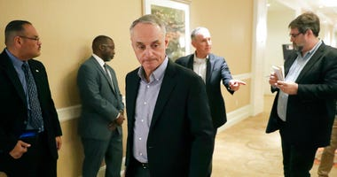 MLB Commissioner Rob Manfred, center, leaves a press conference during MLB baseball owners meetings, Thursday, Feb. 6, 2020, in Orlando, Fla.