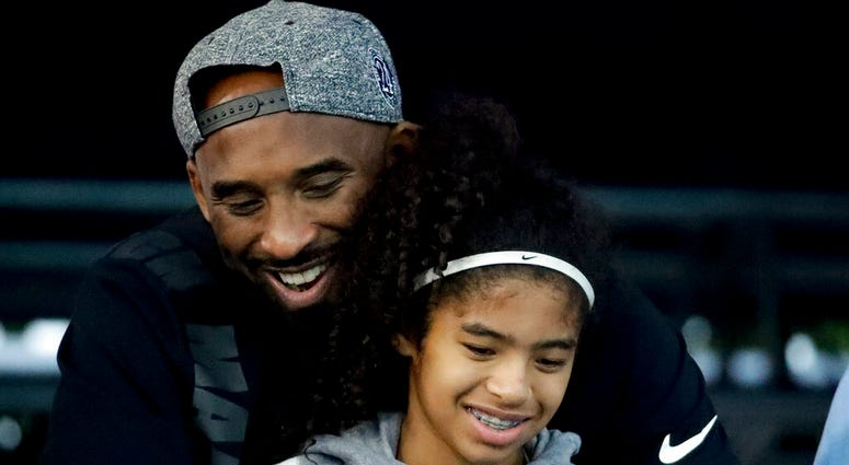 Kobe Bryant and his daughter Gianna watch during the U.S. national championships swimming meet in Irvine, Calif. Federal investigators say wreckage from the helicopter that crashed last month and killed Bryant, his daughter and seven others did not show a
