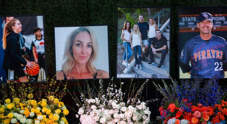Flowers and photos honor members of the Altobelli family outside Angel Stadium, Monday, Feb. 10, 2020, in Anaheim, Calif. Coach John Altobelli, 56, far right, his wife, Keri, 43, second from left, and his daughter Alyssa, 13, left, died in a helicopter cr