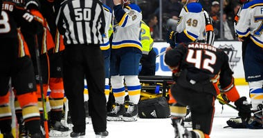 St. Louis Blues defenseman Vince Dunn, left, of center wipes his faces as Anaheim Ducks defenseman Josh Manson kneels on the ice while blues defenseman Jay Bouwmeester, who suffered a medical emergency, is worked on by medical personnel during the first p