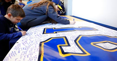 Fans sign a banner sending well wishes to St. Louis Blues' Jay Bouwmeester prior to the start of an NHL hockey game against the Nashville Predators Saturday, Feb. 15, 2020, in St. Louis. Bouwmeester suffered a cardiac episode while on the bench during a g