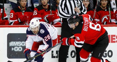 New Jersey Devils defenseman Will Butcher (8) defends against Columbus Blue Jackets right wing Oliver Bjorkstrand (28) during the first period of an NHL hockey game Sunday, Feb. 16, 2020, in Newark, N.J.