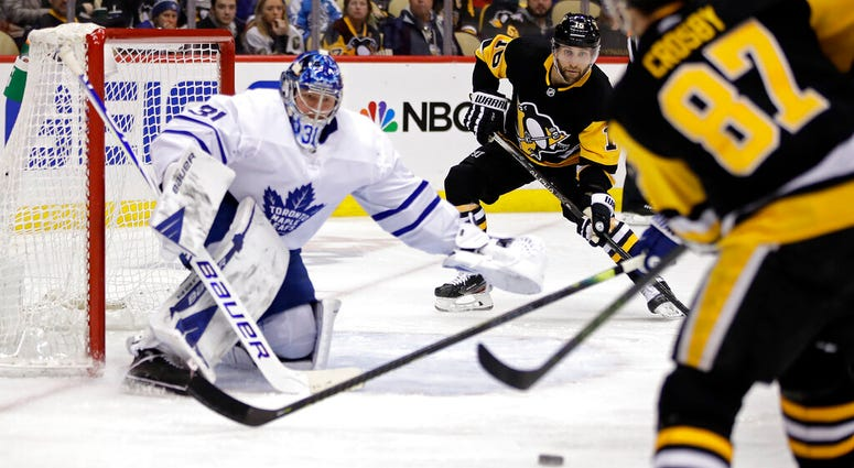 Pittsburgh Penguins' Sidney Crosby (87) passes to Jason Zucker (16) who put a shot behind Toronto Maple Leafs goaltender Frederik Andersen (31) for a goal during the second period of an NHL hockey game in Pittsburgh, Tuesday, Feb. 18, 2020.