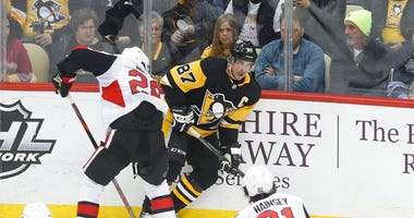 Pittsburgh Penguins' Sidney Crosby (87) looks to pass as Ottawa Senators' Connor Brown defends during the first period of an NHL hockey game, Tuesday, March 3, 2020, in Pittsburgh.