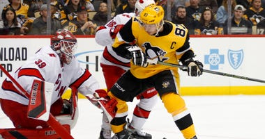 The puck gets behind Pittsburgh Penguins' Sidney Crosby (87) as he tries to gain position infant of Carolina Hurricanes goaltender Alex Nedeljkovic (39).