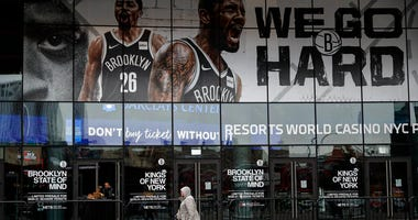 A pedestrian passes an entrance to the Barclays Center in the Brooklyn borough of New York on Thursday, March 12, 2020, after the NCAA's Atlantic 10 Conference Tournament was announced cancelled due to concerns over the COVID-19 coronavirus.