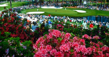 golf fans watch practice on the par three 16th hole during a practice round for the Masters at Augusta National Golf Club in Augusta, Ga.