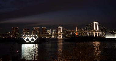 The Olympic rings float in the water near the Rainbow Bridge in the Odaiba section of Tokyo, Monday, March 23, 2020. The Tokyo Olympics are going to happen — but almost surely in 2021 rather than in four months as planned. (AP Photo/Jae C. Hong