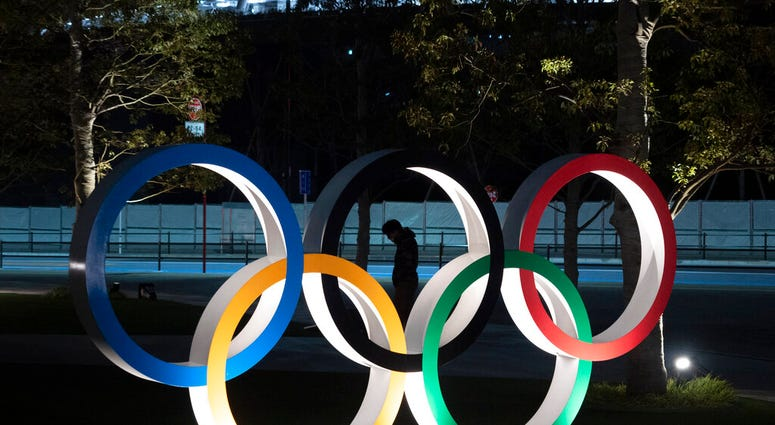"""A man is seen through the Olympic rings in front of the New National Stadium in Tokyo, Tuesday, March 24, 2020. IOC President Thomas Bach has agreed """"100%"""" to a proposal of postponing the Tokyo Olympics for about one year until 2021 because of the coronav"""