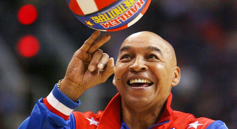 """Harlem Globetrotters' Fred """"Curly"""" Neal performs during a timeout in the second quarter in an NBA basketball game"""
