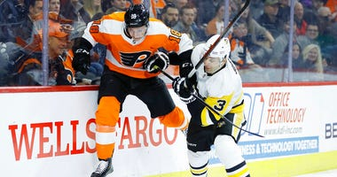 Philadelphia Flyers' Tyler Pitlick, left, tries to jump past Pittsburgh Penguins' Jack Johnson