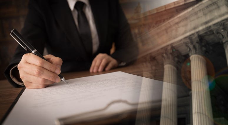 lawyer or attorney signing legal document and agreement with court background. legislation law legal concept