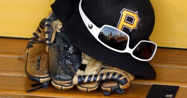 A detailed view of a Pittsburgh Pirates hat and glove before a game at PNC Park in Pittsburgh