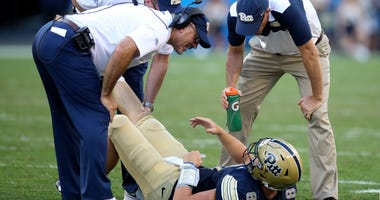 Pittsburgh Panthers quarterback Kenny Pickett (8) is attended to by team trainers and head coach Pat Narduzzi (L) after suffering an apparent leg injury against the Albany Great Danes