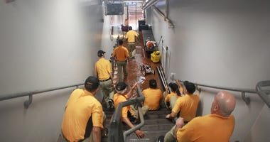 The Pittsburgh Pirates grounds crew take action as rain floods the umpire tunnel during a rain delay of the game between the Milwaukee Brewers and the Pittsburgh Pirates at PNC Park.