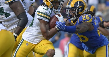 Green Bay Packers running back Aaron Jones (33) is defended by Los Angeles Rams linebacker Mark Barron (26)