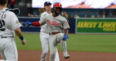 Philadelphia Phillies center fielder Andrew McCutchen (right) grabs at his knee after being tagged out by San Diego Padres starting pitcher Eric Lauer