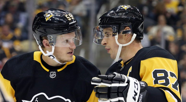 Pittsburgh Penguins center Jake Guentzel and center Sidney Crosby talk before a power play