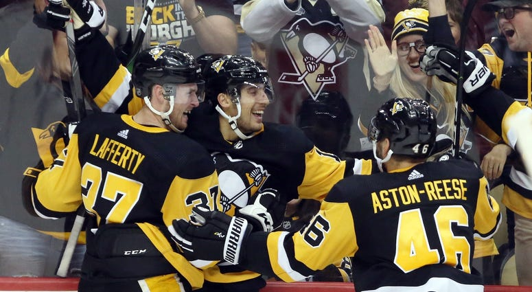 Pittsburgh Penguins left wing Brandon Tanev (middle) celebrates his game winning goal with center Sam Lafferty (37) and center Zach Aston-Reese (46) against the Colorado Avalanche in overtime at PPG PAINTS Arena.