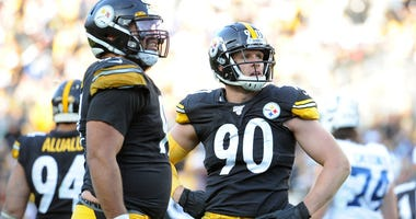 Pittsburgh Steelers linebacker T.J. Watt (90) and defensive end Cameron Heyward (97) watch a replay against the Indianapolis Colts during the fourth quarter at Heinz Field. The Steelers won 26-24.