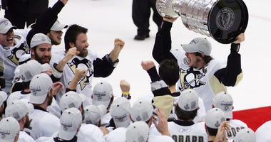 Pittsburgh Penguins center Sidney Crosby (top right) celebrates with teammates after receiving the Stanley Cup following game seven of the 2009 Stanley Cup finals against the Detroit Red Wings a