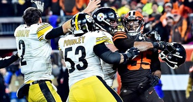Cleveland Browns defensive end Myles Garrett (95) hits Pittsburgh Steelers quarterback Mason Rudolph (2) with his own helmet as offensive guard David DeCastro (66) tries to stop Garrett during the fou...
