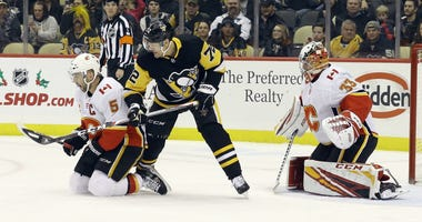 Calgary Flames defenseman Mark Giordano (5) and Pittsburgh Penguins right wing Patric Hornqvist (72) battle for the puck in front of Flames goaltender David Rittich (33) during the first period at PPG Paints Arena