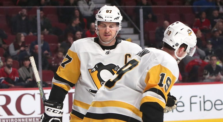 Pittsburgh Penguins center Jared McCann (19) celebrates his goal in a Montreal Canadiens empty net with teammate center Sidney Crosby (87) during the third period at Bell Centre.