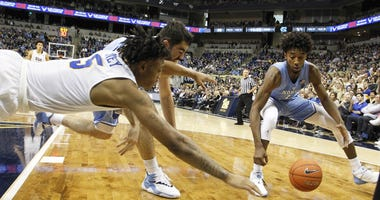 Pittsburgh Panthers guard Au'Diese Toney (5) dives for a loose ball against North Carolina Tar Heels forward Luke Maye (32) and guard Leaky Black (1) during the second half at the Petersen Events Center