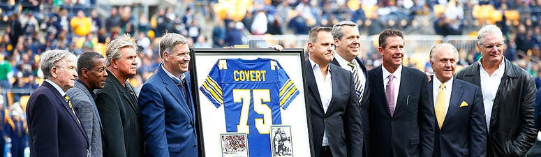 Former Pittsburgh Panthers player Jimbo Covert is surrounded by his former teammates after having his number retired at halftime between the Pittsburgh Panthers