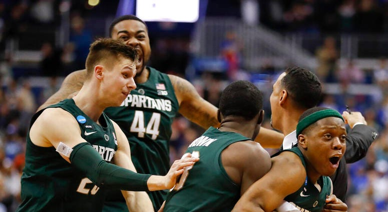 Michigan State guard Cassius Winston, right, celebrates with teammates Matt McQuaid (20), Nick Ward (44) and Gabe Brown (13) after defeating Duke in an NCAA men's East Regional final college basketball game in Washington, Sunday, March 31, 2019.