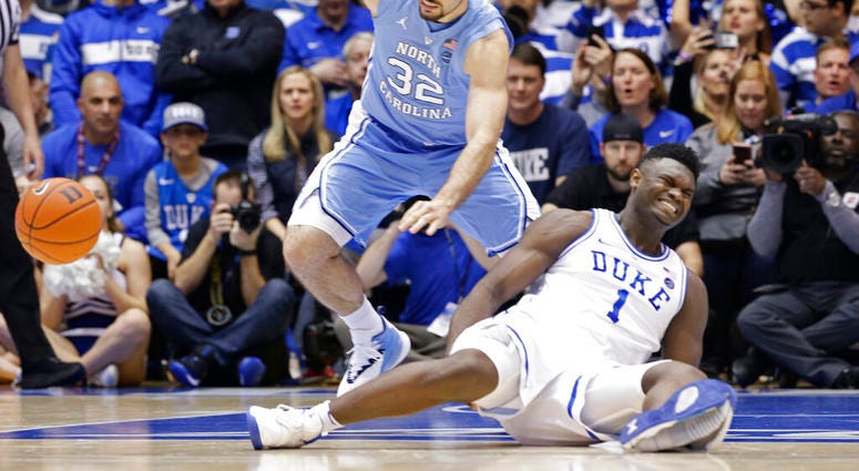 Duke's Zion Williamson (1) falls to the floor with an injury while chasing the ball with North Carolina's Luke Maye (32) during the first half of an NCAA college basketball game in Durham, N.C., Wednesday, Feb. 20, 2019.