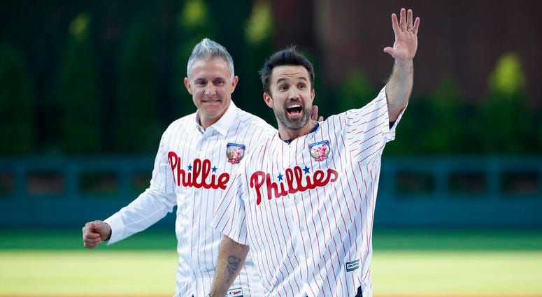 """Actor Rob McElhenney, right, one of the creators of """"It's Always Sunny in Philadelphia,"""" reacts after catching a ceremonial first pitch from former Philadelphia Phillies player Chase Utley"""