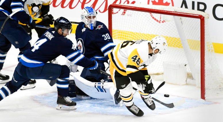 Pittsburgh Penguins' Zach Aston-Reese scores against Winnipeg Jets goaltender Laurent Brossoit