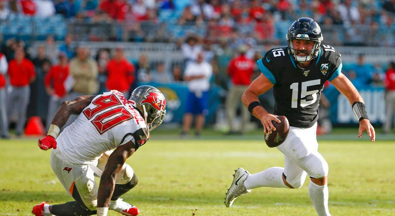Jacksonville Jaguars quarterback Gardner Minshew (15) scrambles away from Tampa Bay Buccaneers linebacker Jason Pierre-Paul (90) during the second half of an NFL football game, Sunday Dec. 1, 2019, in Jacksonville, Fla.