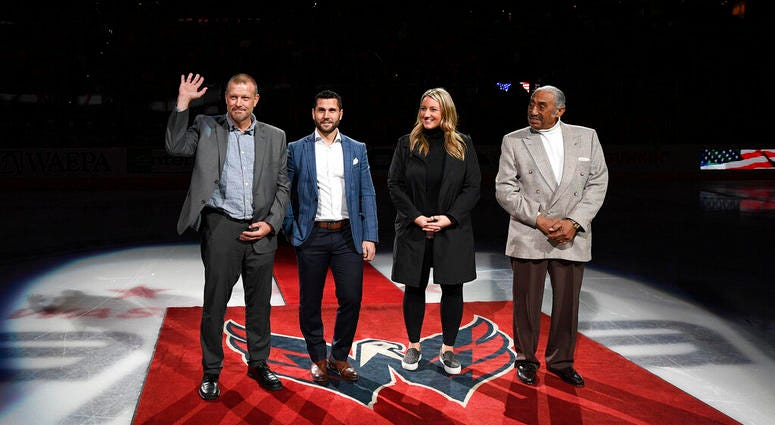 The 2019 U.S. Hockey Hall of Fame class, from left to right, Tim Thomas, Brian Gionta, Krissy Wendell and Neal Henderson stand on the ice before a ceremonial puck drop ahead of an NHL hockey game