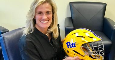 Pitt AD Heather Lyke with women's lacrosse goalie helmet in 2018