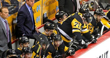 Pittsburgh Penguins coach Mike Sullivan, rear second from left, and assistant Sergei Gonchar, left, stand behind their bench as Evgeni Malkin (71) waits to take the ice, during the third period in Game 4 of an NHL hockey first-round playoff series against